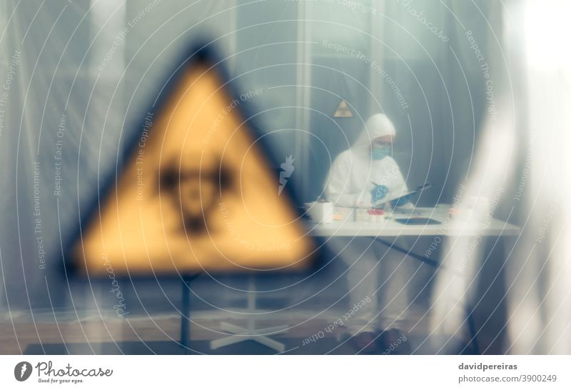 Scientist investigating in the laboratory behind a protective curtain protection curtain scientist isolation coronavirus biohazard symbol