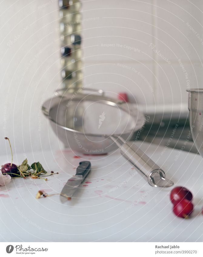 knife with sieve and cherries in white kitchen Summer Red Fruit Juicy Organic food Delicious Knives messy Dripping Silver White Fresh ripe Garden Seasons