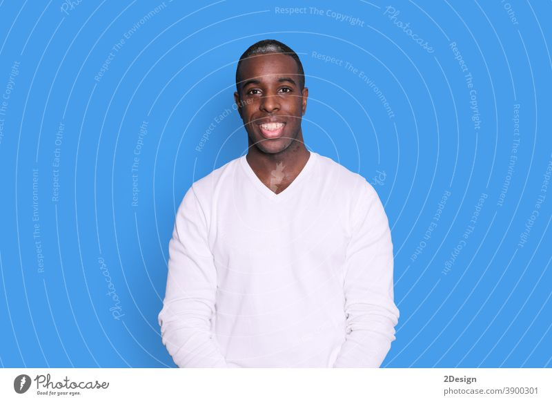 Smiling young african american man guy in casual white sweater posing isolated on pastel blue background studio portrait. People sincere emotions lifestyle concept. Mock up copy space. Looking camera.