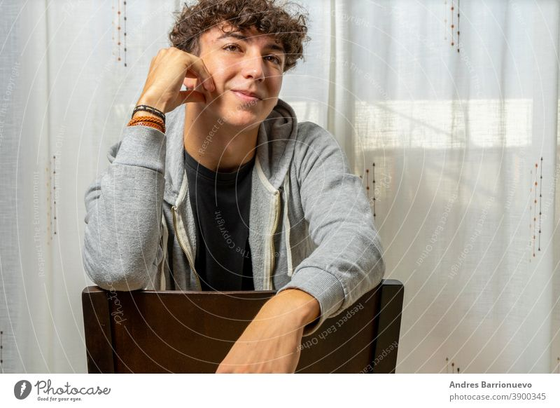 Attractive young man with curly hair wearing gray sweatshirt posing on white curtains background cheerful casual smile male adult handsome happy attractive