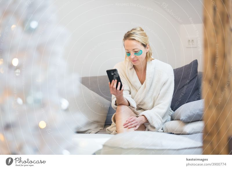 Woman at home relaxing on sofa couch using social media on phone for video chatting with her loved ones during corona virus pandemic. Stay at home, social distancing lifestyle.