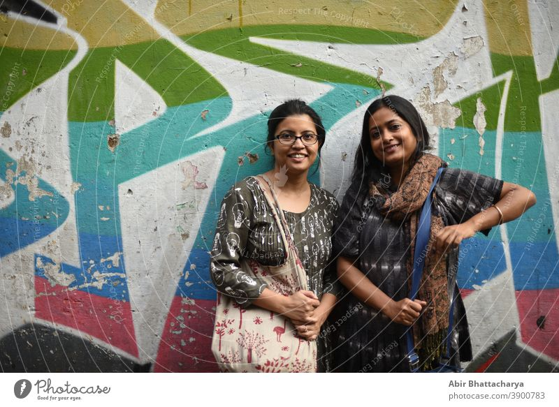 Portrait of two Indian Bengali brunette women/friends/sisters in front of a graffiti wall. Indian lifestyle actress adult asian attractive background beautiful