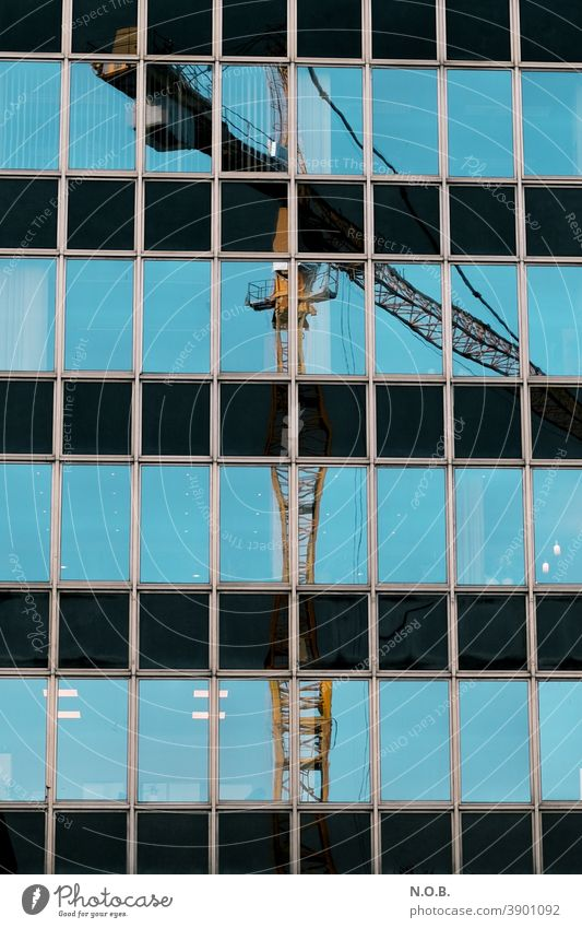 Reflection of a crane in an office façade Crane Construction site Sky Blue Exterior shot Work and employment Build Workplace Economy Technology Profession