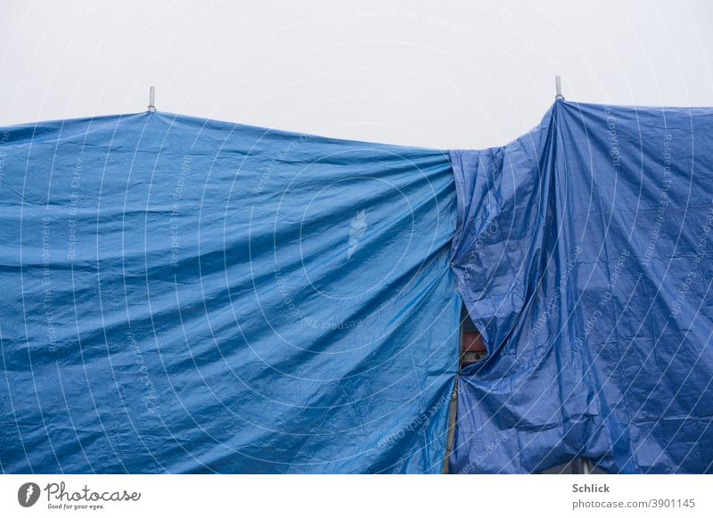 Hides scaffolding and roof covered with blue plastic tarpaulins Protection from rain Blue construction shrouded Colour photo Exterior shot Deserted