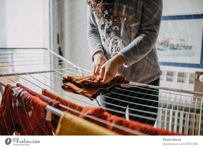 Woman drying clothes indoor Clothesline clothes horse indoors Domestic domestic life house Household Housekeeping Mother motherhood at home Laundry