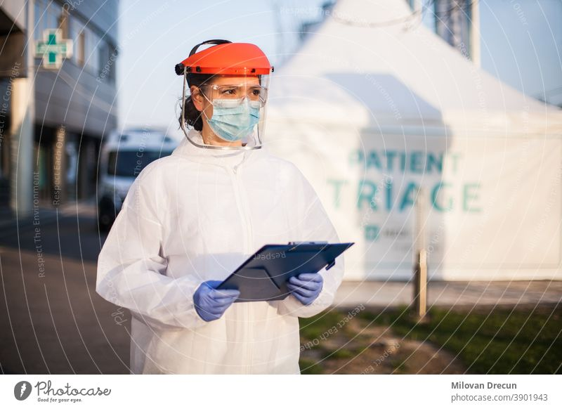 Paramedic wearing personal protective equipment PPE holding folder standing in front of ICU hospital isolation rt-PCR drive thru testing site,COVID-19 pandemic outbreak crisis,worried exhausted staff