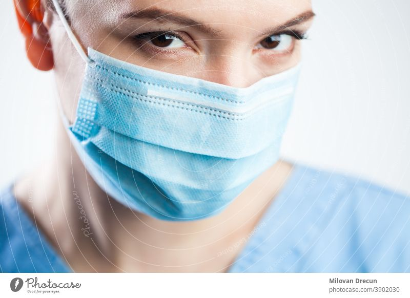 Young woman closeup detail headshot,wearing blue scrubs & protective face mask,attractive beautiful caucasian female doctor staring at camera,pretty eyes giving significant look,Coronavirus COVID-19