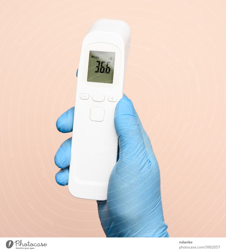 hand in blue latex gloves hold an electronic thermometer to measure temperature technology test tool treatment virus white body check checkup contactless