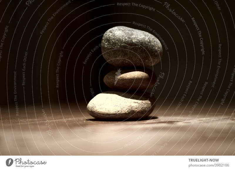 Three pebbles lie in balance on a dimly lit table in front of a dark background, as if floating on top of each other, and symbolize the connection between heaven and earth or spirit and matter.