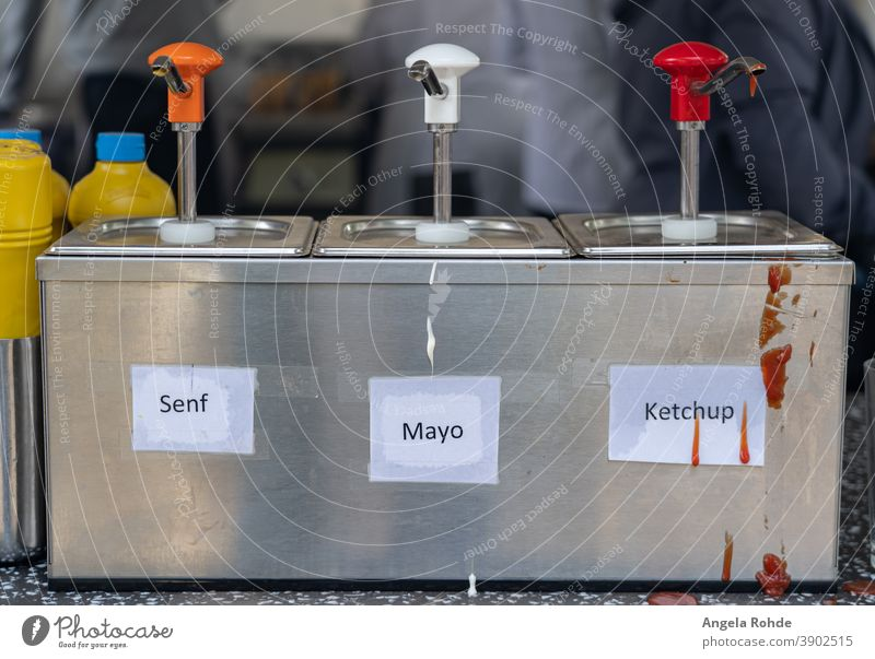 Dispenser for mustard, mayonnaise and ketchup at a sausage stand, with the German words for mustard, mayonnaise and ketchup Donor Mustard Mayonnaise Ketchup