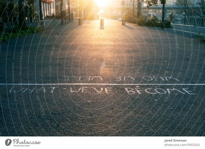 Who we were, What we've become - Inspirational message on the streets of Lyon Quote Street inspirational street sign Meaningful black asphalt Road marking Sign
