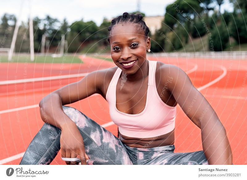 Athlete sprinter sitting on the athletics track athlete ethnic afro afroamerican train training sportswear athleticism female runner running competition fit