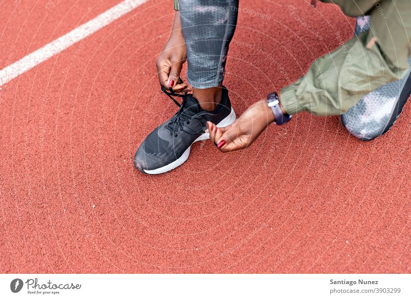 Athlete sprinter tying her shoes starting race competition athlete athletics competitive ready line beginnings compete competitor olympic olympics run sports