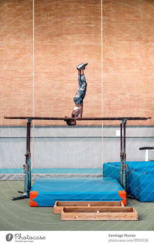 Athlete practicing on parallel bars acrobatic action active activity athlete athletics balance body daylight effort energy equipment exercise fit flexibility