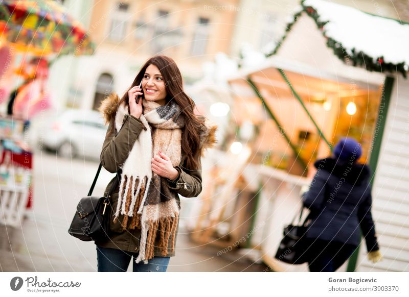 Happy fashion woman using a smart phone on street in winter at Christmas market attractive beautiful christmas new year cellphone city device female happy