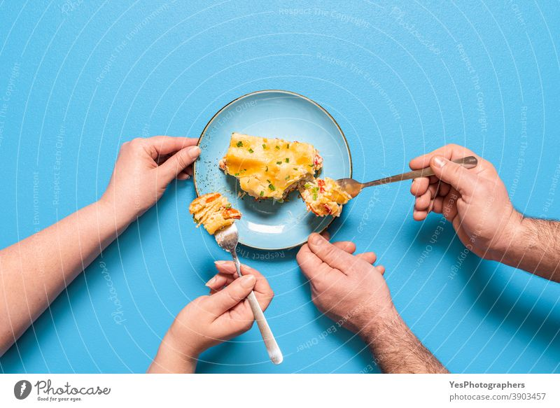 Vegetarian lasagna slice, top view. People eating a piece of lasagna above view baked goods bechamel sauce blue background carbs carrots cheese comfort food