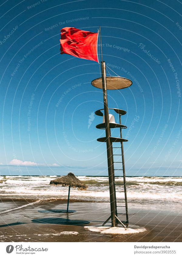 Lifeguard tower with flag on seashore lifeguard rescue beach seaside wave symbol summer seascape ocean observe coast coastline season seacoast blue sky