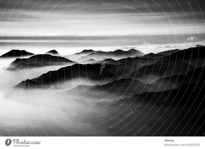 layering of mountains and clouds one peak sky alps landscape fog nature outdoor italy view rock summer europe scenery blue water lake garda alpine background