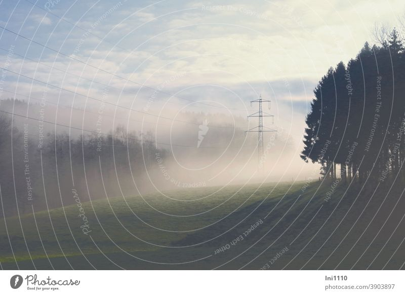 Winter landscape with fog and sunshine Fog natural spectacle Beautiful weather Hill Valley Forest trees Shadow Sunbeam Landscape Electricity pylon Power lines