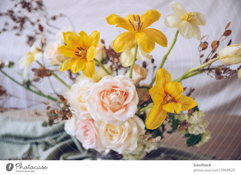 Still life with a beautiful bouquet of flowers table vase wedding decoration white close up yellow background interior arrangement dinner romantic pink rose