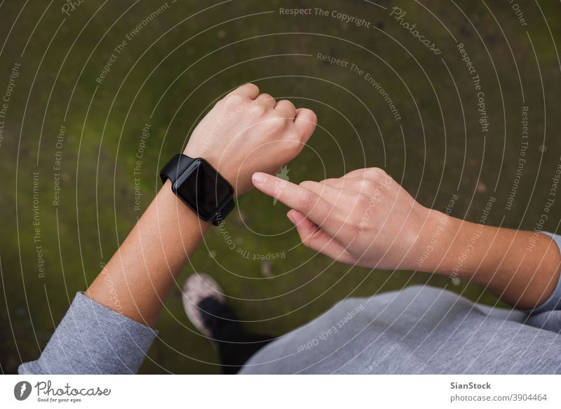 Close up of young woman checking the smartwatch device, outdoors. fitness sport health athlete touch touching technology heart runner workout healthy exercise