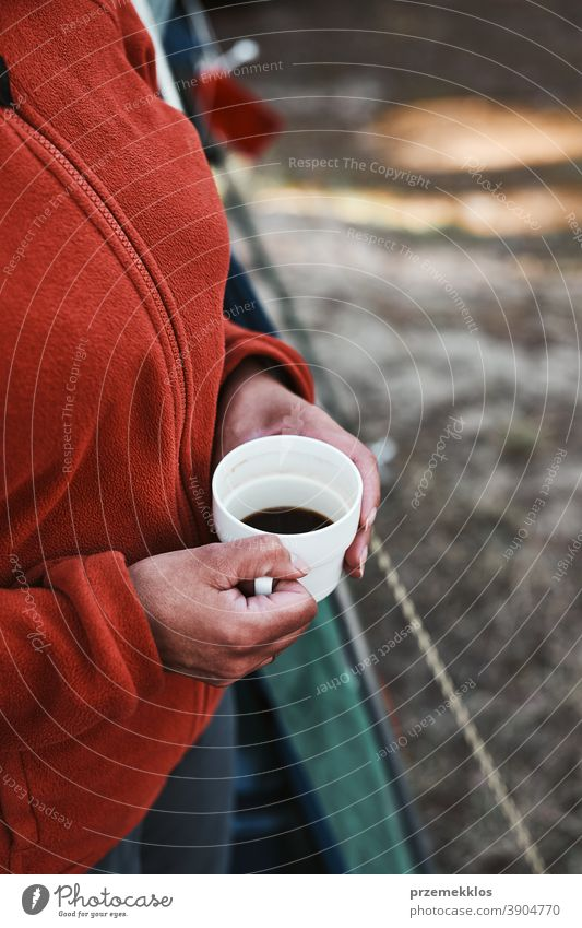 Close up of woman sitting outdoors holding cup with coffee above hiker wanderer trip wanderlust exploration lifestyle picnic camp freedom vacation travel