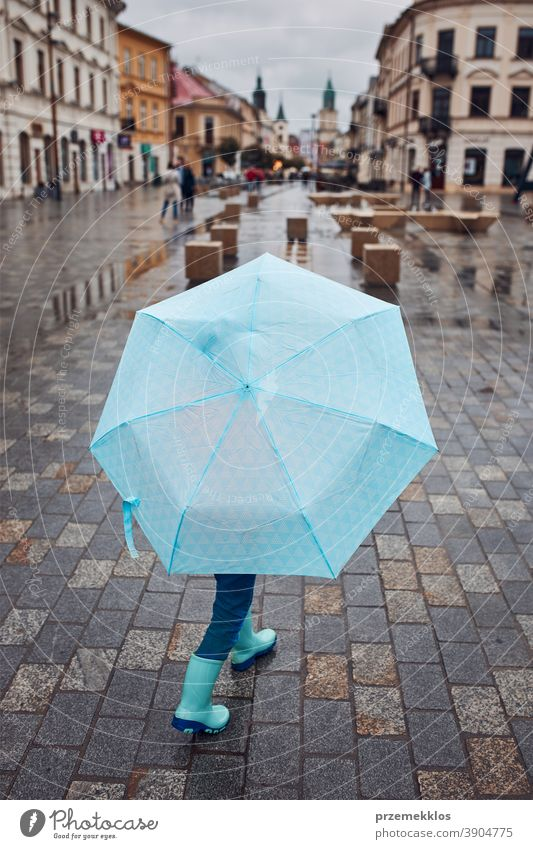 Child holds large blue umbrella in his hand and walks through the city centre on a rainy, gloomy autumn day rains Outdoors Little Autumn seasonal To fall