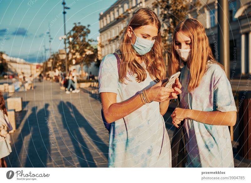 Young women girls using smartphones wearing the face masks to avoid virus infection caucasian cellphone conversation covid-19 female lifestyle mobile outbreak