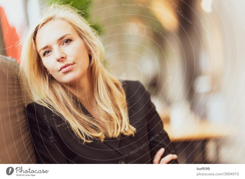 the young woman in the cafe looks friendly into the camera Young woman smiling woman Lifestyle Fashion Elegant Face of a woman Looking into the camera Feminine