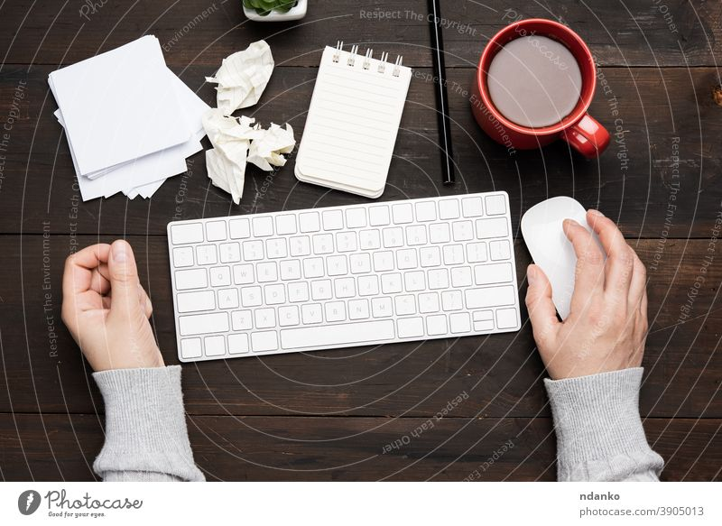 white wireless keyboard and mouse on a wooden brown table, next to a white cup with coffee business office computer workplace caucasian hand background notebook