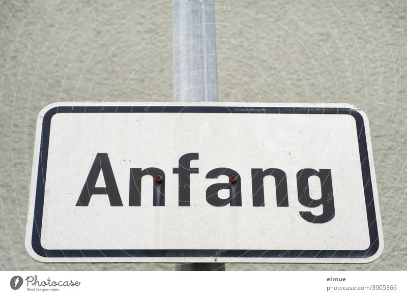 "the white, framed metal plate reads ""Anfang"" in black block letters / Anbruch / Beginning start sign Communication Starting point rudiment beginning of the end"