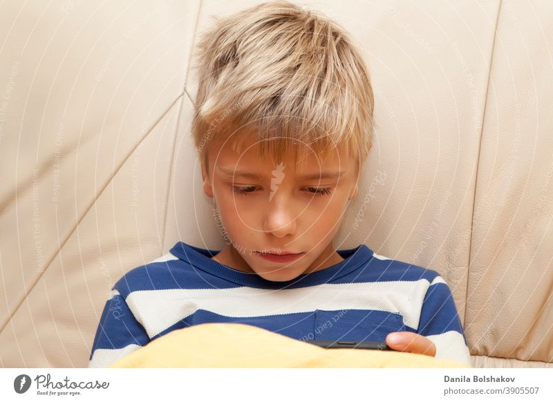 Little kid playing game or watching something on mobile smart phone bed bedtime boy caucasian cell phone cellphone child childhood communication connection cute