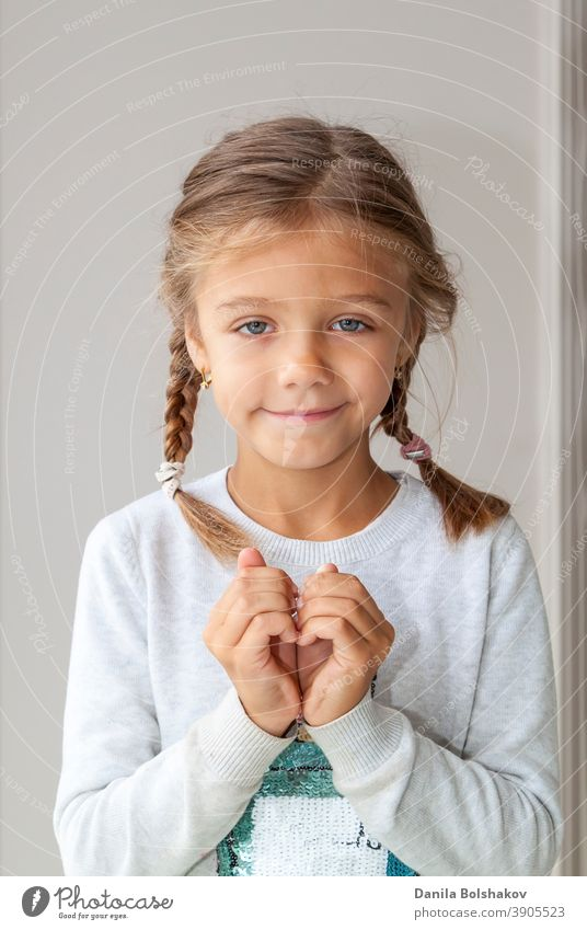 Portrait of cute little girl showing hand heart gesture, sweet precious child making body language, love, positive feeling and emotion adorable arms baby