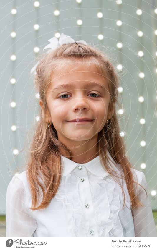 Portrait of cute charming little caucasian girl in white blouse and bow with background of glowing light bulbs people bright blur attractive shiny glitter