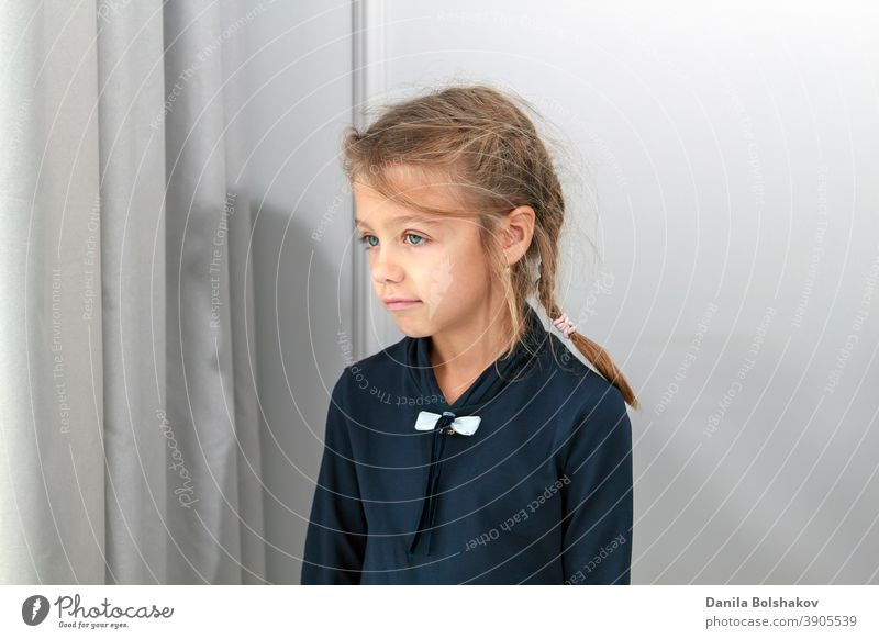 small girl looks into distance through brightly lit window behind curtain alone beauty bored calm casual caucasian child childhood concept coronavirus cute