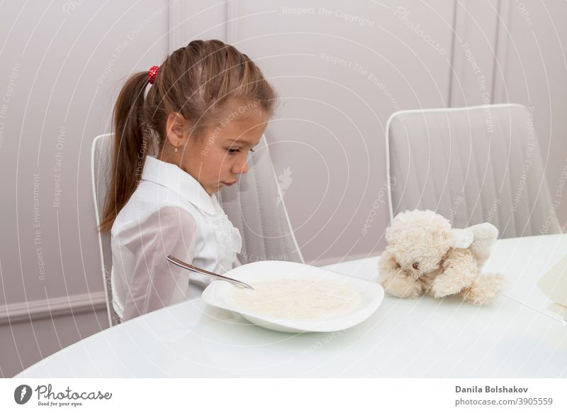 child is sitting at glass table in huge bright dining room near panoramic window. girl turned away from porridge with disgruntled face before going to school