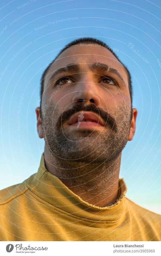 Portrait of young man in front of sunset sky waring yellow jumper Eyebrow Moustache mustache Peaceful enjoyment thinking lifestyle casual cheerful people love
