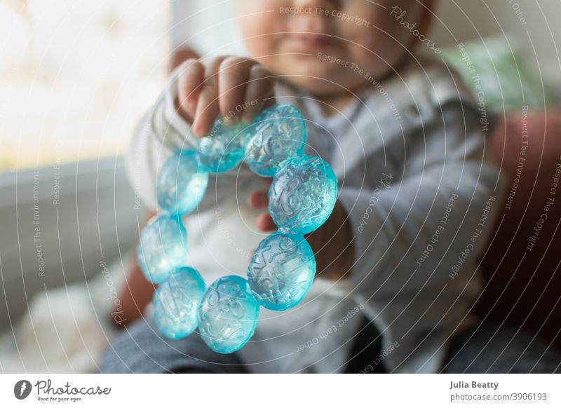 6 month old baby holding out blue teething ring in hands chew chewing six months 6 months infant grasp explore sensory water cold plastic toy development child