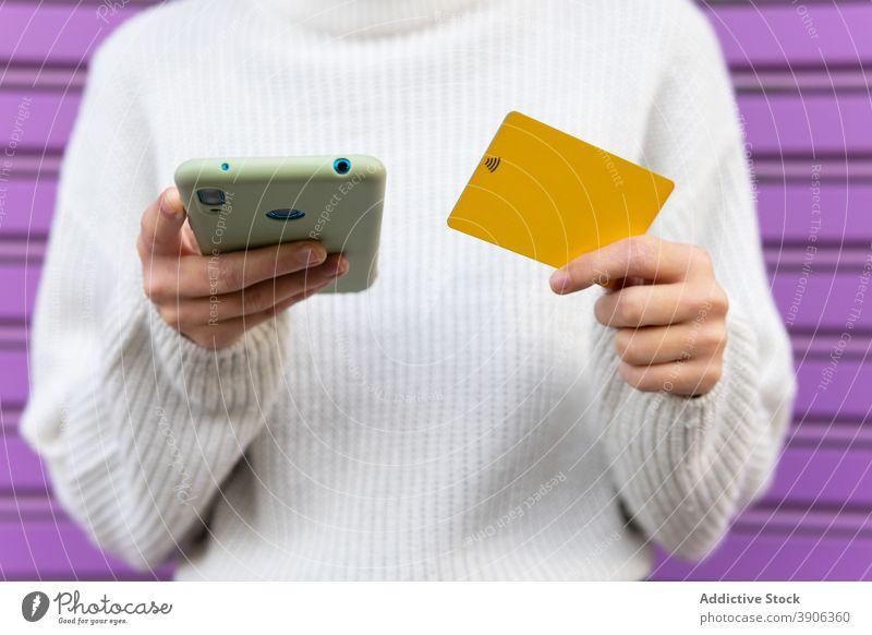 Crop woman making online payment via smartphone plastic card wireless purchase order e commerce female shopper device internet money customer gadget finance