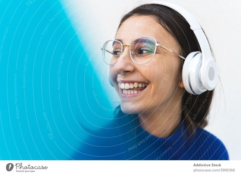Positive woman listening to music in headphones on street cheerful song millennial sound carefree female glad young gadget happy smile purple building wall