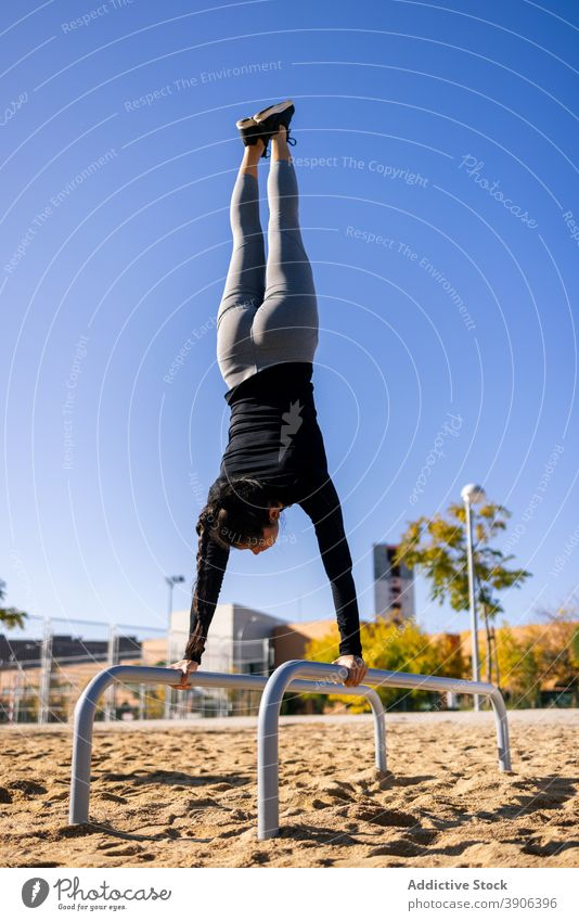 Strong sportswoman balancing on parallel bars in splits handstand calisthenics training balance strong effort female athlete fit practice fitness vitality slim