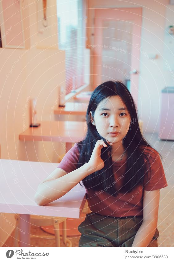 Young asian teen cute millennial girl looking at the camera and sitting in pastel pink cafe, lifestyle concept one loneliness rest calm woman alone leisure