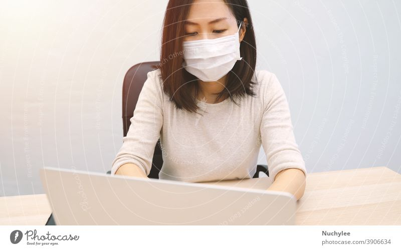 Young asian woman wearing hygienic mask using computer laptop in home office, prevent the pandemic of Covid-19 and Coronavirus, work from home and self quarantine concept