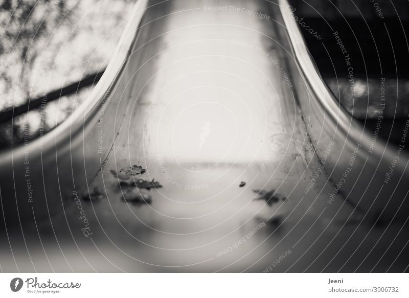 Close-up of a stainless steel slide on a playground | autumn leaves lying lonely on the slide surface | gloomy mood Slide Skid High-grade steel Playing