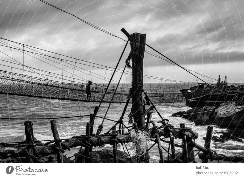 One fishing man takes the challenge walking on a swinging rope foot bridge to a rock island with big dangerous waves at Pantai Timang beach, Java, Indonesia in black and white monochrome grayscale. It looks like a scene in Pirates of the Caribbean.