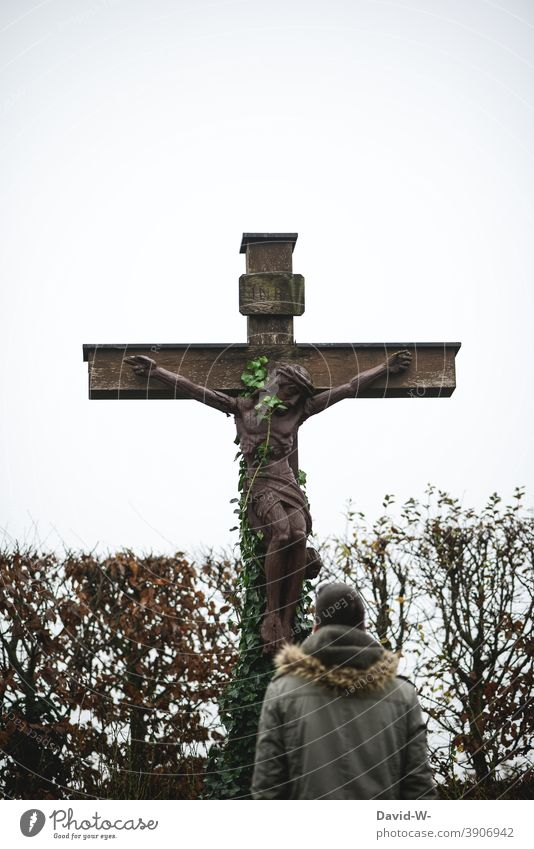 Man standing in front of an old cross surrounded by climbing plants Crucifix Religion and faith God oblivion Hope Christian cross Jesus Christ pray