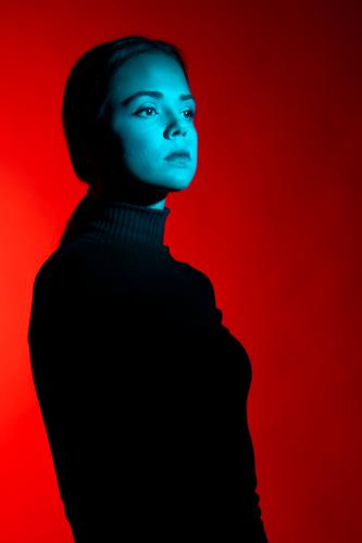 Close up portrait of young woman in the studio with red and blue lights wearing all black outfit body isolated dark glamour one studio shot studio lighting gel
