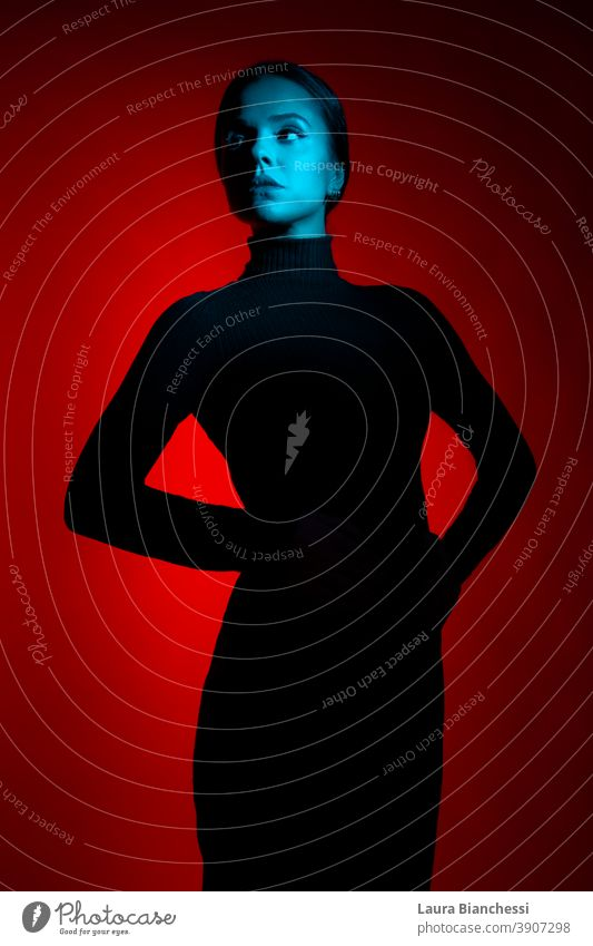 Portrait of young woman power posing in the studio with red and blue lights wearing all black outfit body isolated dark glamour one studio shot studio lighting