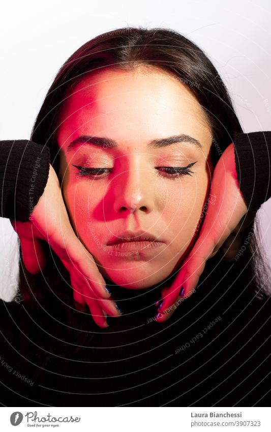 Studio portrait of a sad young woman with pink shadows and hands framing her face beauty fashion beautiful hair black model brunette dark eyes person glamour