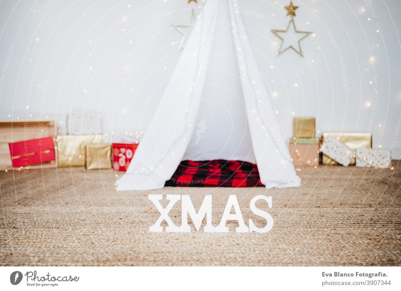 Christmas decoration at home, lights, teepee and presents. Christmas time christmas tent plaid blanket december decorated white tree house indoors holiday